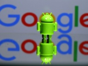 3D printed Android mascot Bugdroid is seen in front of a Google logo in this illustration