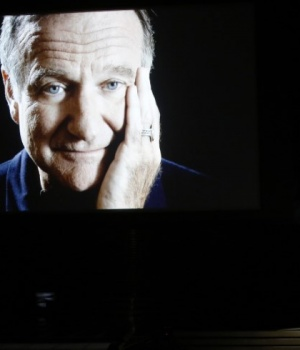 Billy Crystal takes the stage to pay tribute to Robin Williams, shown on a large screen, during the 66th Primetime Emmy Awards in Los Angeles