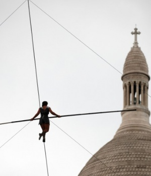 Tightrope walker Tatian-Mosio Bongonga advances on a tightrope as she scales the Monmartre hill towards the Sacre Coeur Basilica in Paris