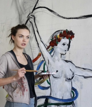 Oksana Shachko, activist of women's rights group Femen, paints a wall of her room in Kiev