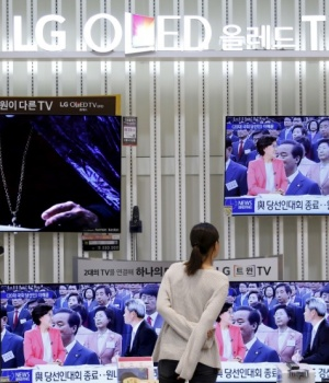 A woman looks at a LG Electronics' organic light-emitting diode (OLED) TV sets, which are made with LG Display flat screens, at its store in Seoul