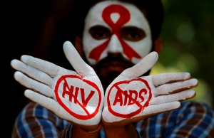 A student displays his hands painted with messages as he poses during an HIV/AIDS awareness campaign to mark the International AIDS Candlelight Memorial, in Chandigarh