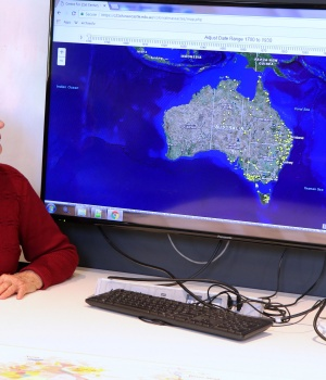 A supplied image shows University of Newcastle research academic, Professor Lyndall Ryan, sitting in front of a screen displaying a map detailing the number of Aboriginal and Torres Strait Islander massacres that occurred on Australia's colonial frontier