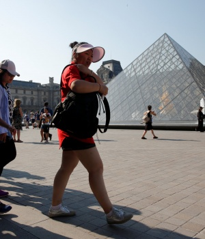 Chinese tourists walk past the Louvre Pyramid designed by Chinese-born U.S. Architect Ieoh Ming Pei outside the Louvre Museum in Paris