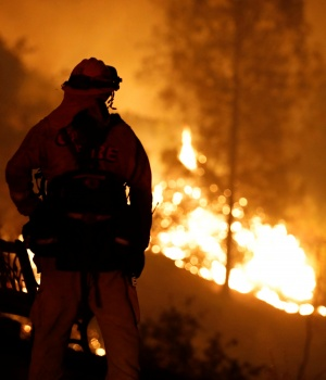 A firefighter watches the flames of the Carr Fire advance as it burns west of Redding
