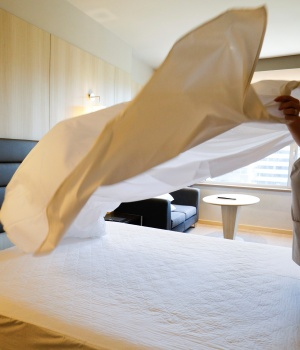 A chambermaid who works at a hotel where chambermaids are members of staff and not associated with the Kellys association, makes a bed in Madrid
