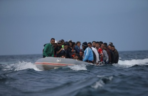 Migrants are seen before disembarking from a dinghy at Del Canuelo beach as they cross the Strait of Gibraltar sailing from the coast of Morocco, in Tarifa