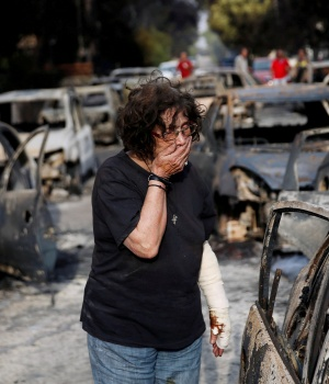 A woman reacts as she tries to find her dog, following a wildfire at the village of Mati, near Athens