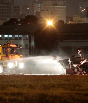 Firefighters work at the site after a small plane crashed at the Campo de Marte airport in Sao Paulo