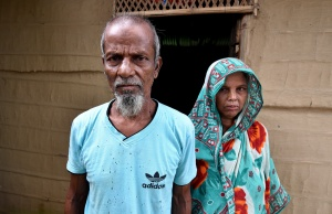 Abdul Suban, a farmer, and his wife pose for a photograph outside their home in Nellie village, in Morigaon district