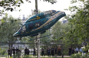 Crane lifts a helicopter after it crashed in Beijing