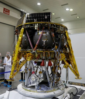 Israeli scientists stand next to an unmanned spacecraft