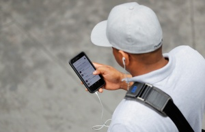 A man holds an Apple iPhone as he walks on a street in New York