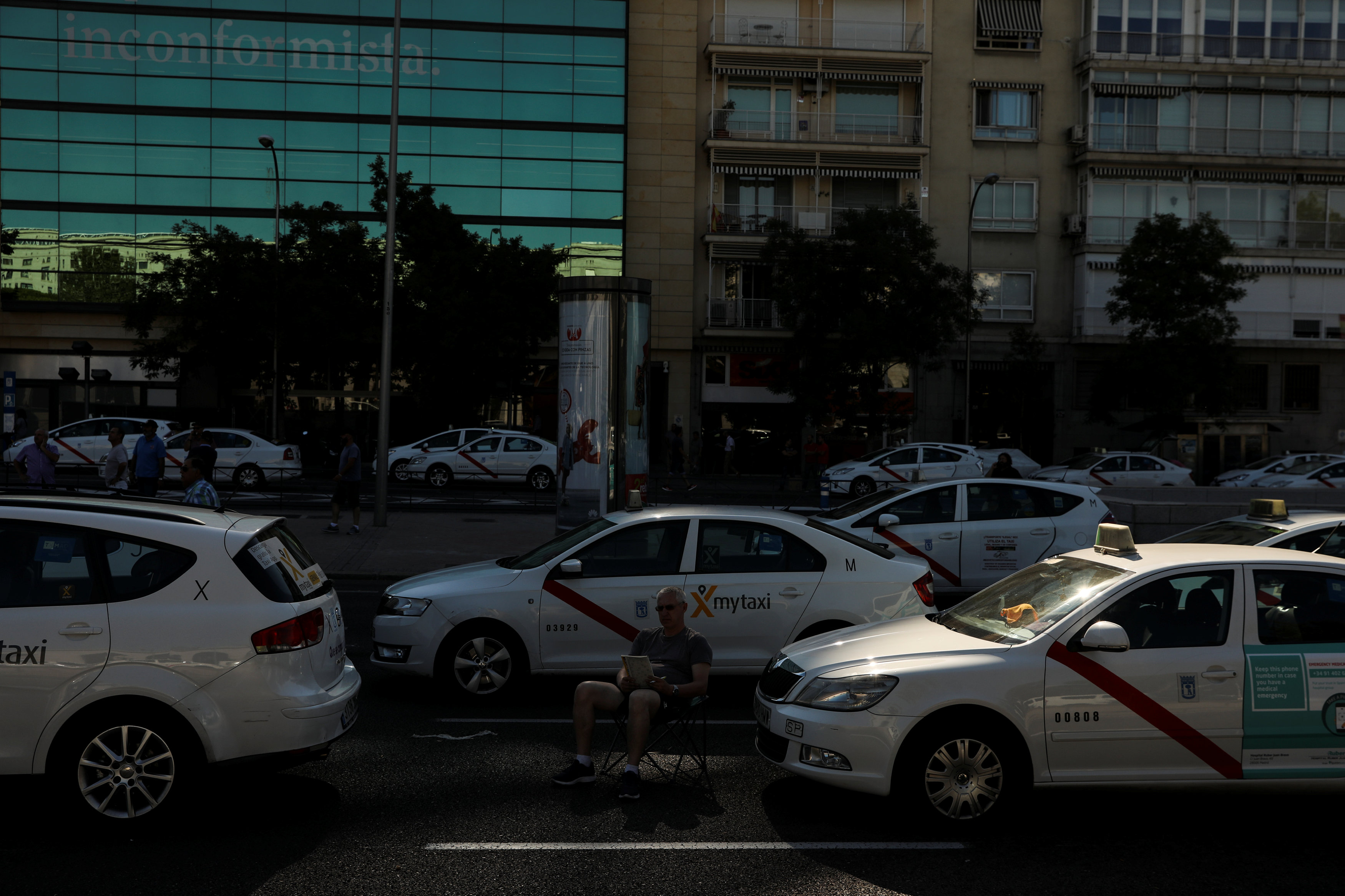 A taxi driver does crossword puzzles as taxis block a section of the main avenue Paseo de la Castellana during an indefinite strike against what they say is unfair competition from ride-hailing and car-sharing services such as Uber and Cabify i