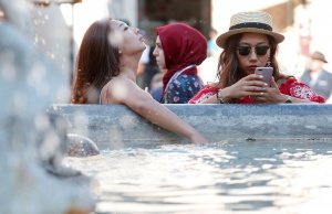 Women cool off in water fountains in Rome as temperatures soar throughout Italy