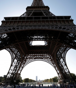 People stand in line at an information booth following the closure of the Eiffel Tower as part of a strike by employees over lengthening queues during the peak summer tourist season in Paris