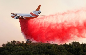 A DC-10 air tanker drops fire retardant along the crest of a hill to protect the two bulldozers below that were cutting fire lines at the River Fire in Lakeport, California