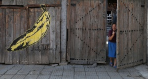 Local villager walks out of her house next to a reproduction of an Andy Warhol art piece in the village of Staro Zhelezare