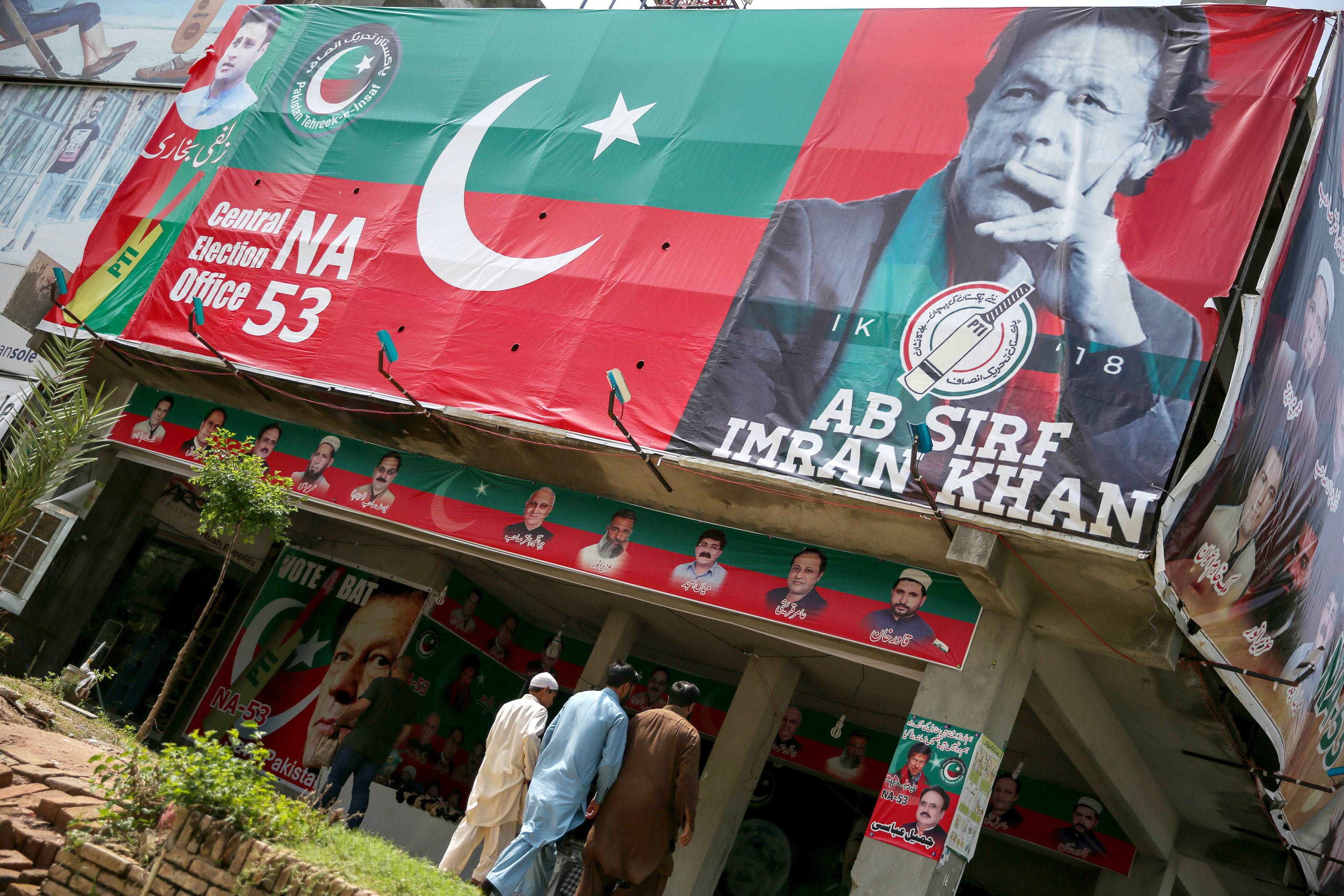 People walk past an image of cricket star-turned-politician Imran Khan, chairman of Pakistan Tehreek-e-Insaf (PTI) at a market in Islamabad