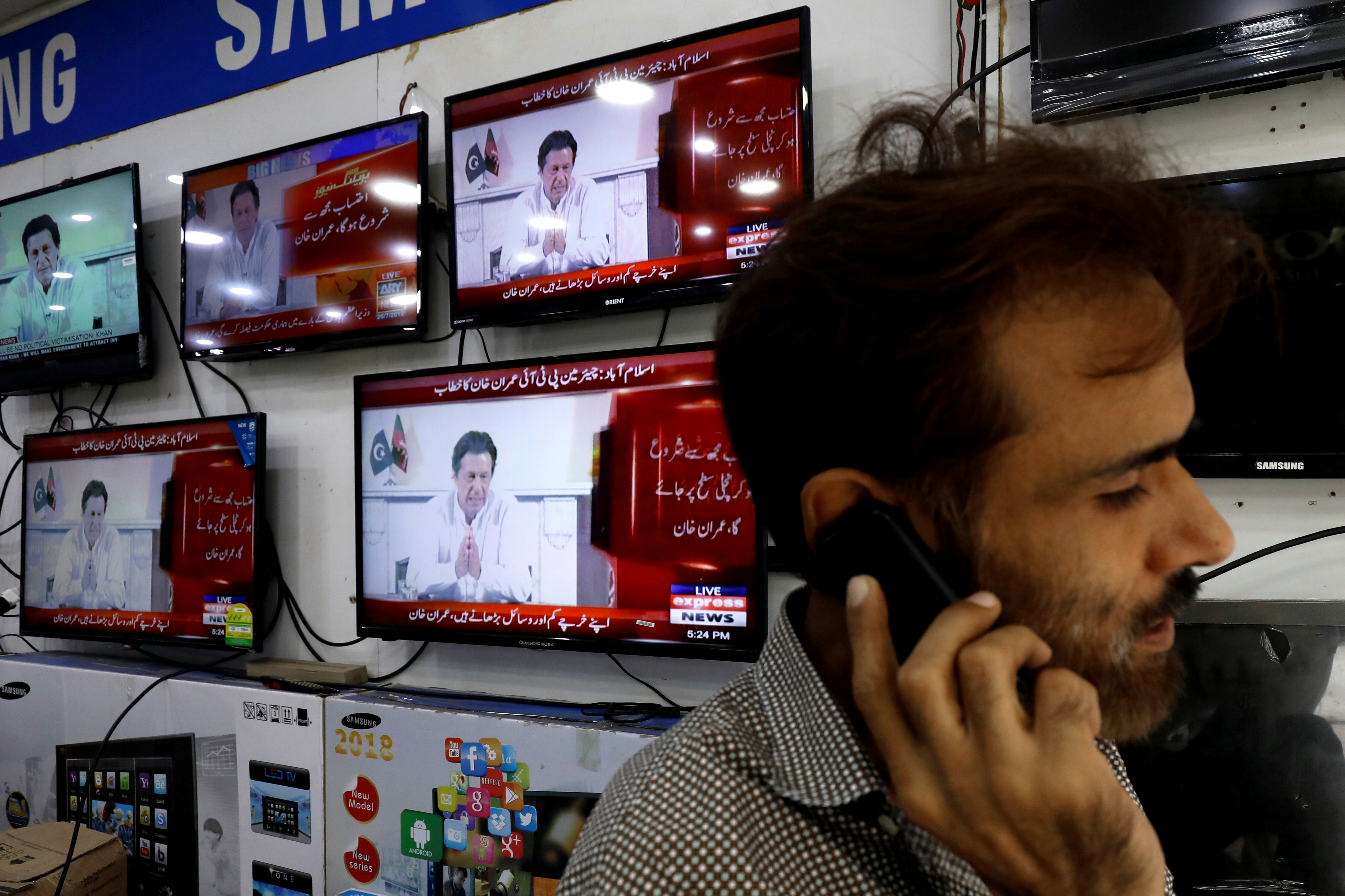 A shopkeeper talks on his mobile phone, with the background of screens displaying the cricket star-turned-politician Imran Khan, chairman of Pakistan Tehreek-e-Insaf (PTI), in a televised speech a day after the general election, at a market in