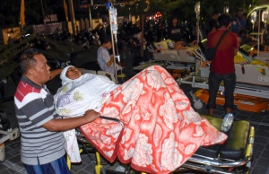 A person injured during a strong earthquake waits for treatment outside the Mataram City hospital with other patients who were evacuated, in Mataram, Lombok island