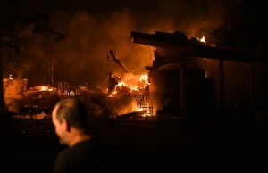 Scott Whitley watches as the Ponderosa Fire burns a garage at his residence east of Oroville