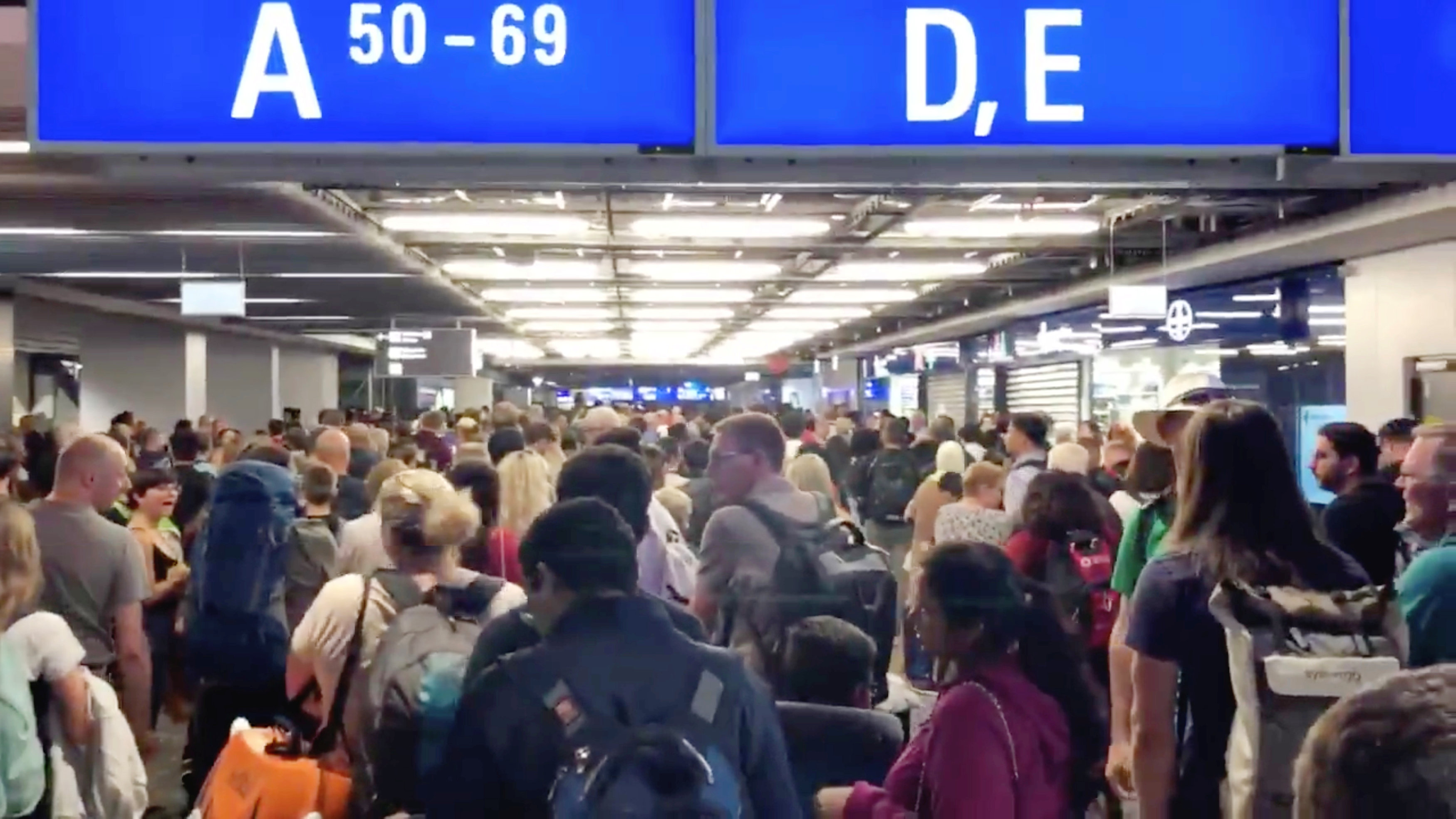 People are seen waiting at the Frankfurt Airport due to the evacuation in Frankfurt