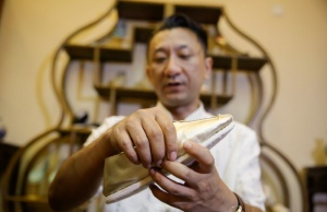 Cobbler Cai Wenke puts the finishing touches to a 'thousand-layer' cloth shoe at the demonstration workshop of the Neiliansheng shoemaker in Beijing