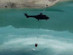 A Swiss Air Force Super Puma helicopter loads water for cows in the Lac d'Hongrin due to an ongoing drought near Chateau d'Oex
