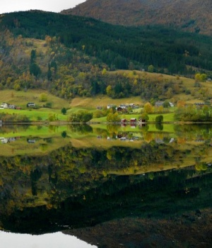Norwegian farms are reflected in the still waters of a fjord iN Norway