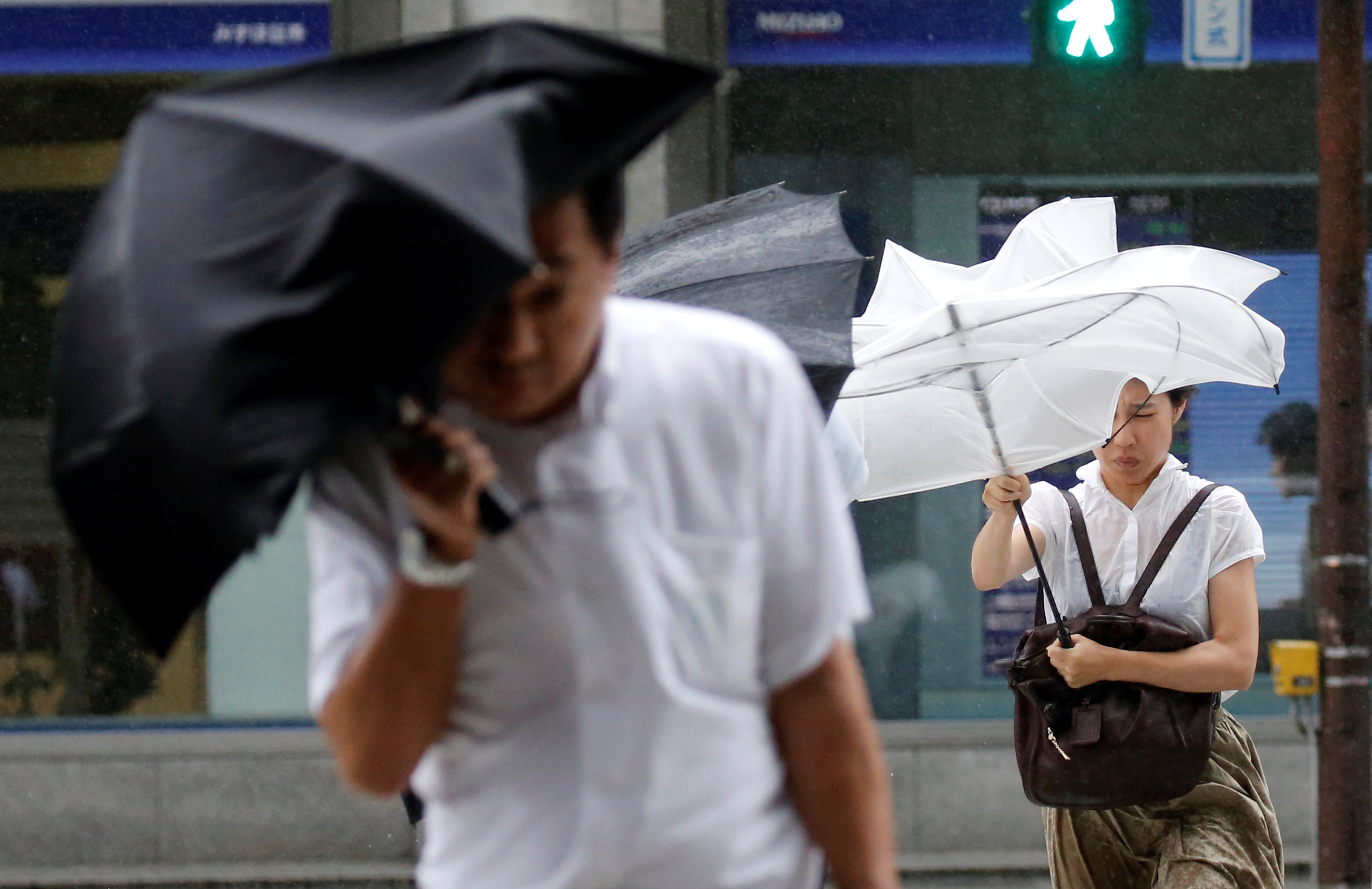 Passersby using an umbrella struggle against a heavy rain and wind as Typhoon Shanshan approaches Japan's mainland in Tokyo
