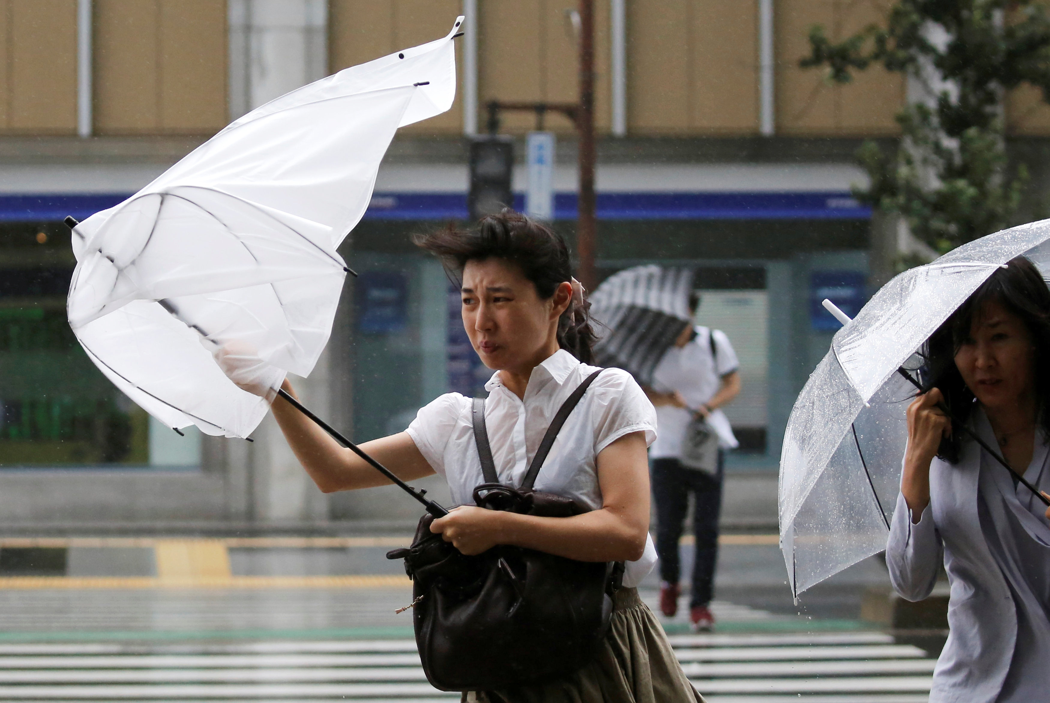 Passersby using umbrellas struggle against a heavy rain and wind as Typhoon Shanshan approaches Japan's mainland in Tokyo