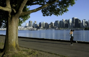 A jogger runs along the seawall in Stanley Park with the city skyline in the background
