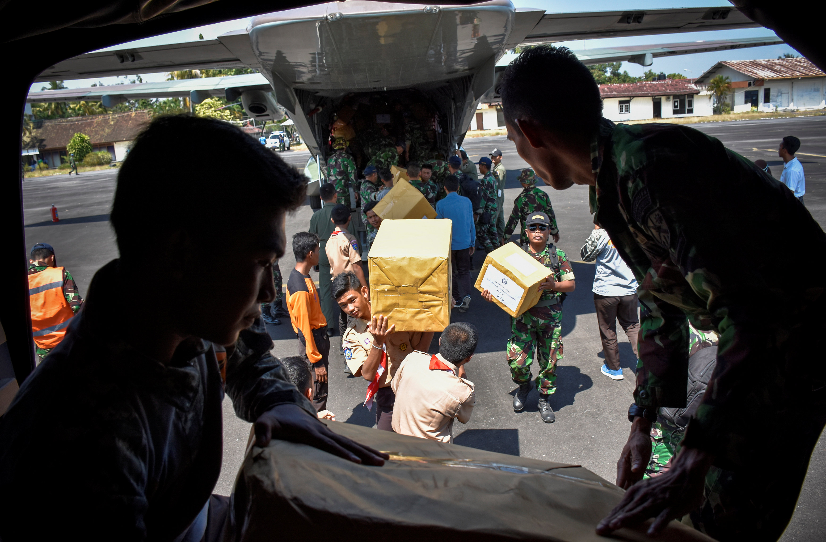 Indonesian soldiers unload relief aid for earthquake victims from a plane at an airbase in Mataram