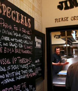 ames Martin, chef at Sydney's Old Fitzroy Hotel, explains to customers next to a menu board about the dish called parmagiana or parma for short, and how proceeds from their order will go to Australian farmers