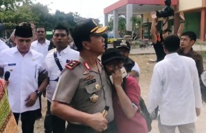 West Java governor and West Nusa Tenggara police standing in a field next to a closed public hospital while the building windows rattle during an earthquake in Lombok