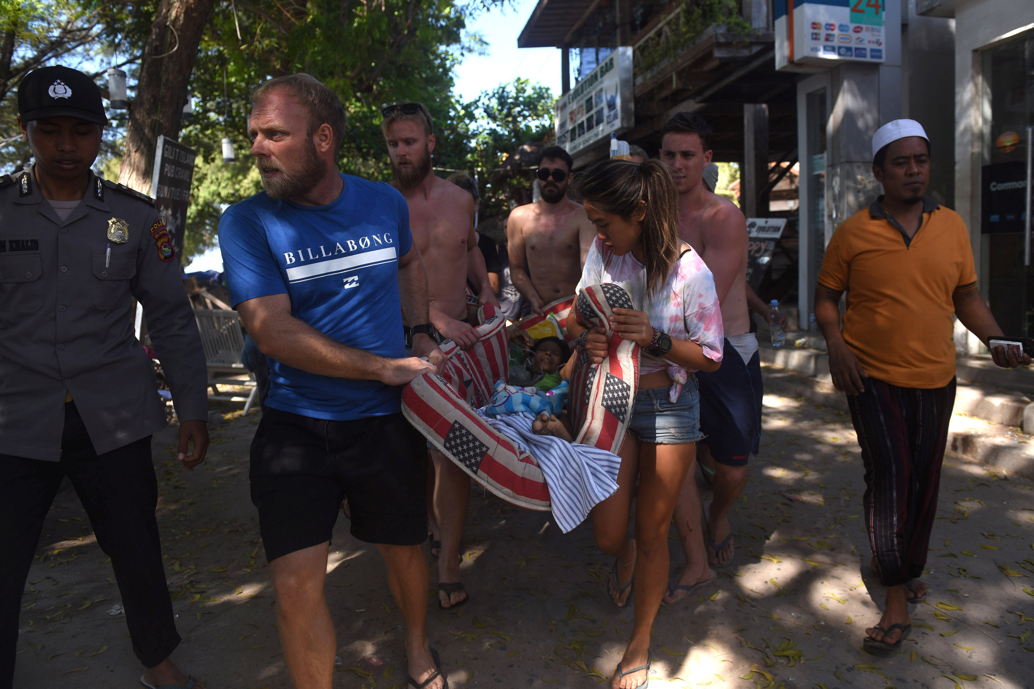Foreigners help to evacuate a woman following Sunday's earthquake on Gili Trawangan, Lombok