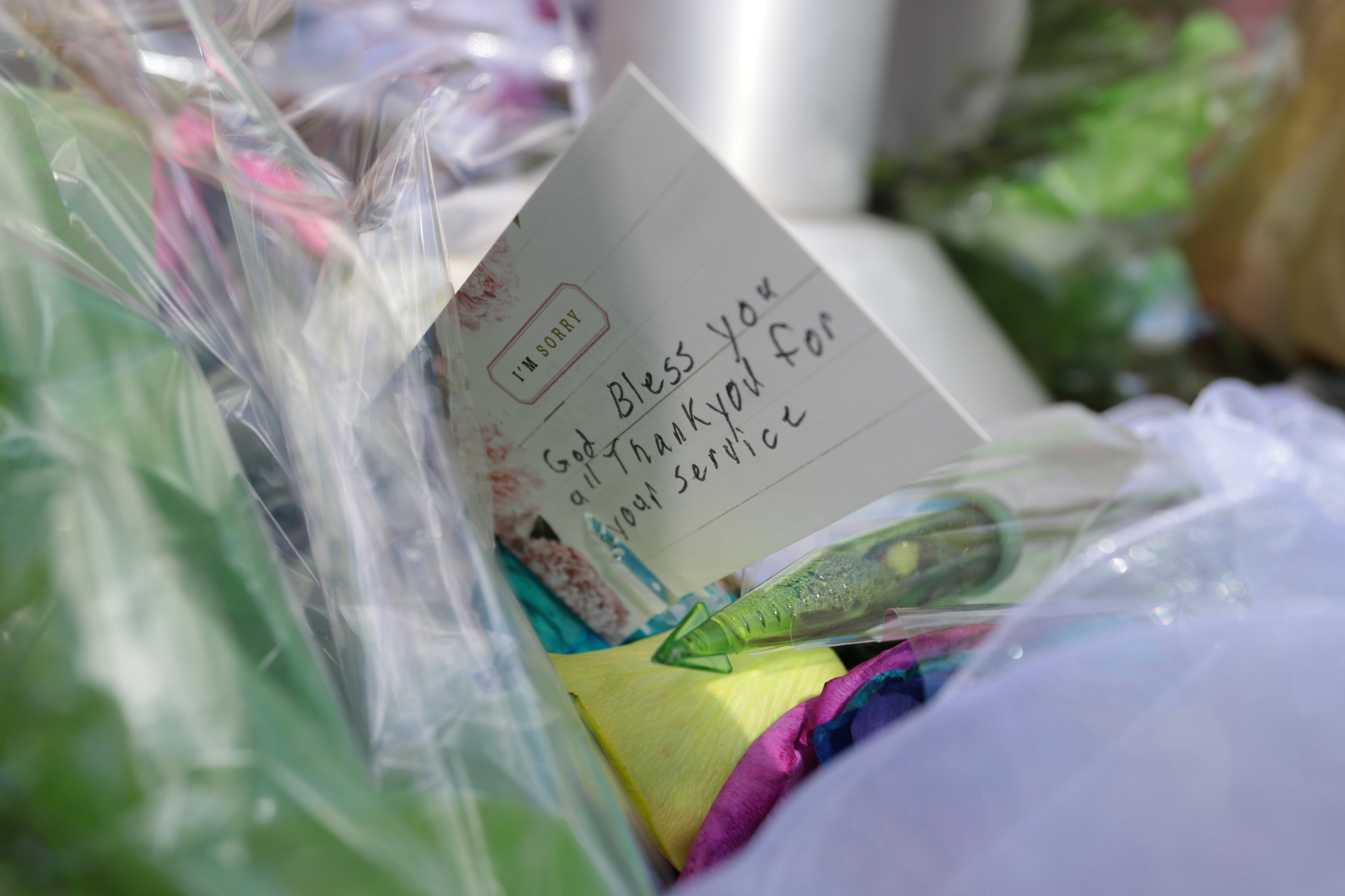 A note left with flowers outside Fredericton Police Headquarters in Fredericton