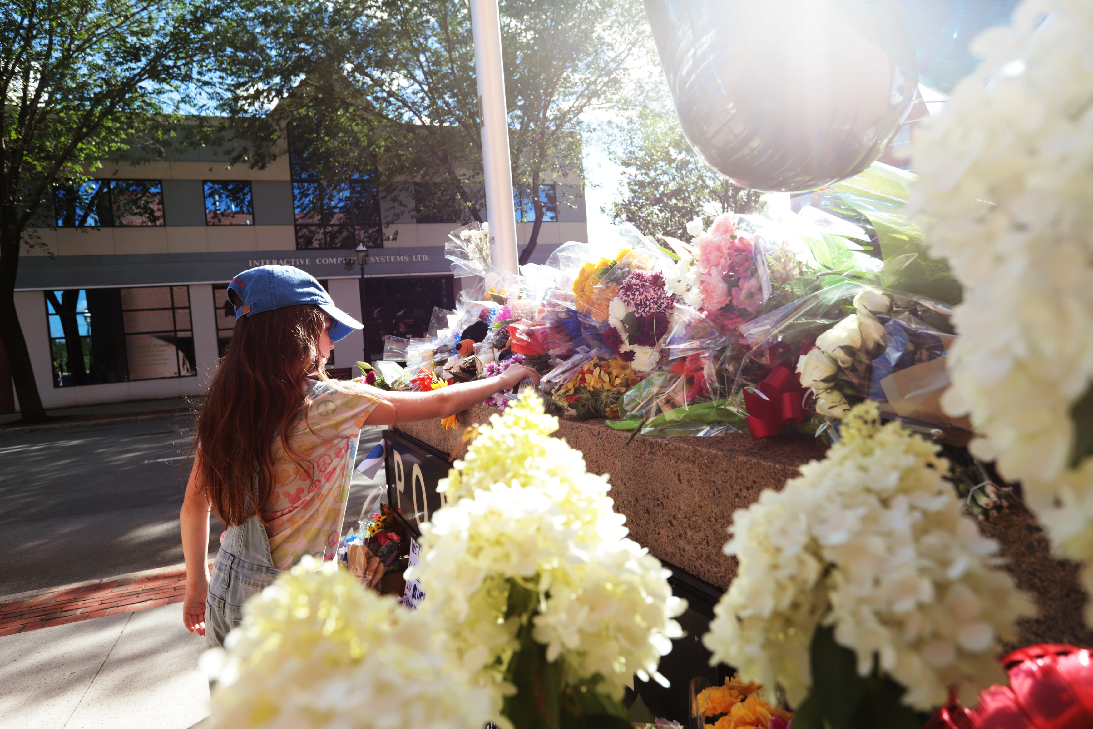 Sophie Davis lays flowers at a shrine that has been created outside Fredericton Police Headquarters in Fredericton