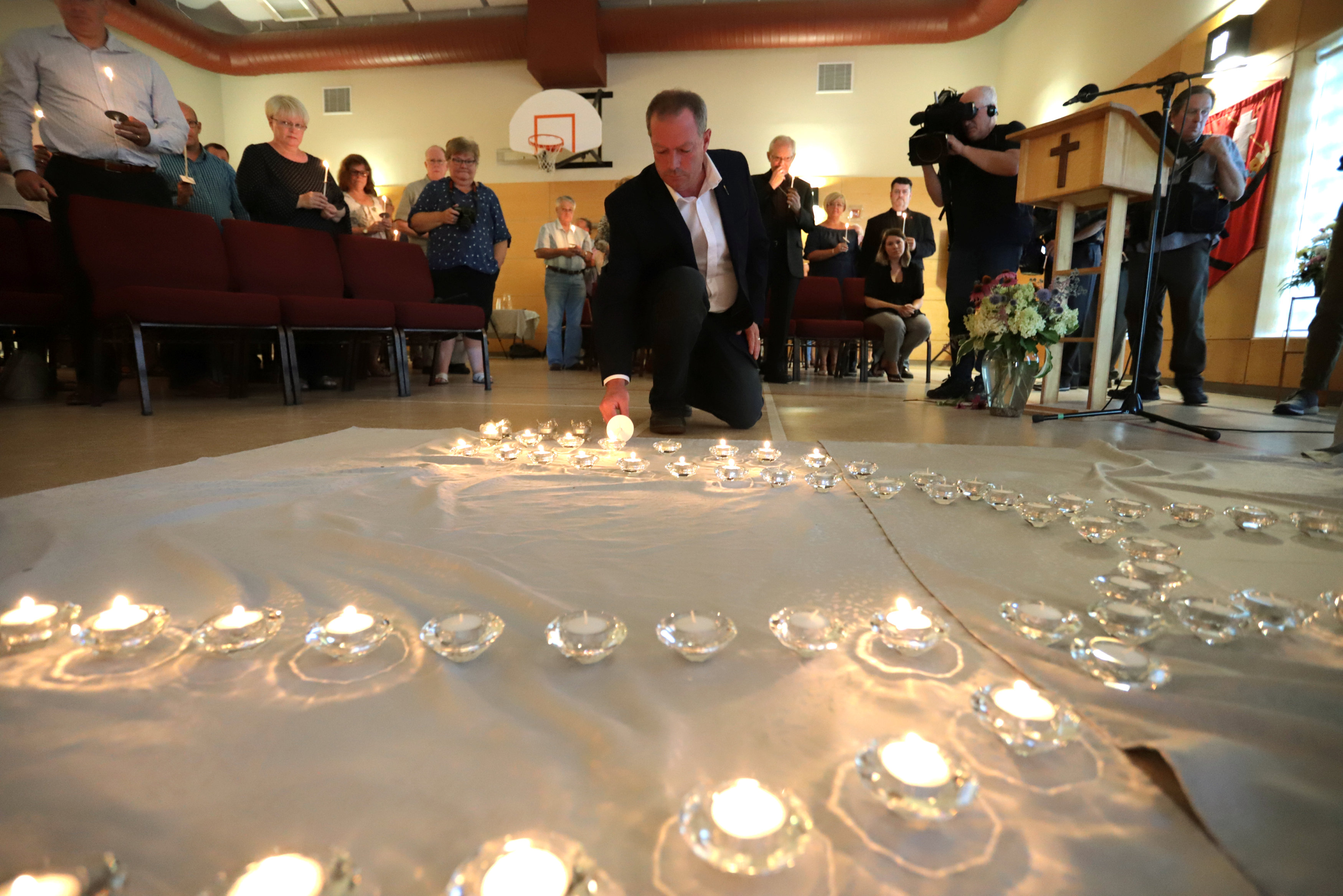 Participants light candles for the fallen at the St. John the Evangelist Anglican Church in Fredericton
