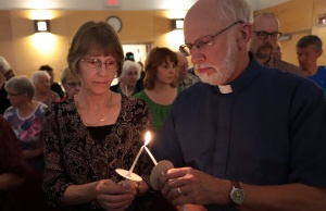 Participants light candles in a vigil at the St. John the Evangelist Anglican Church in Fredericton for the fallen in a fatal shooting in Fredericton