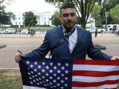 White nationalist leader Jason Kessler holds a flag across from the White House in Washington