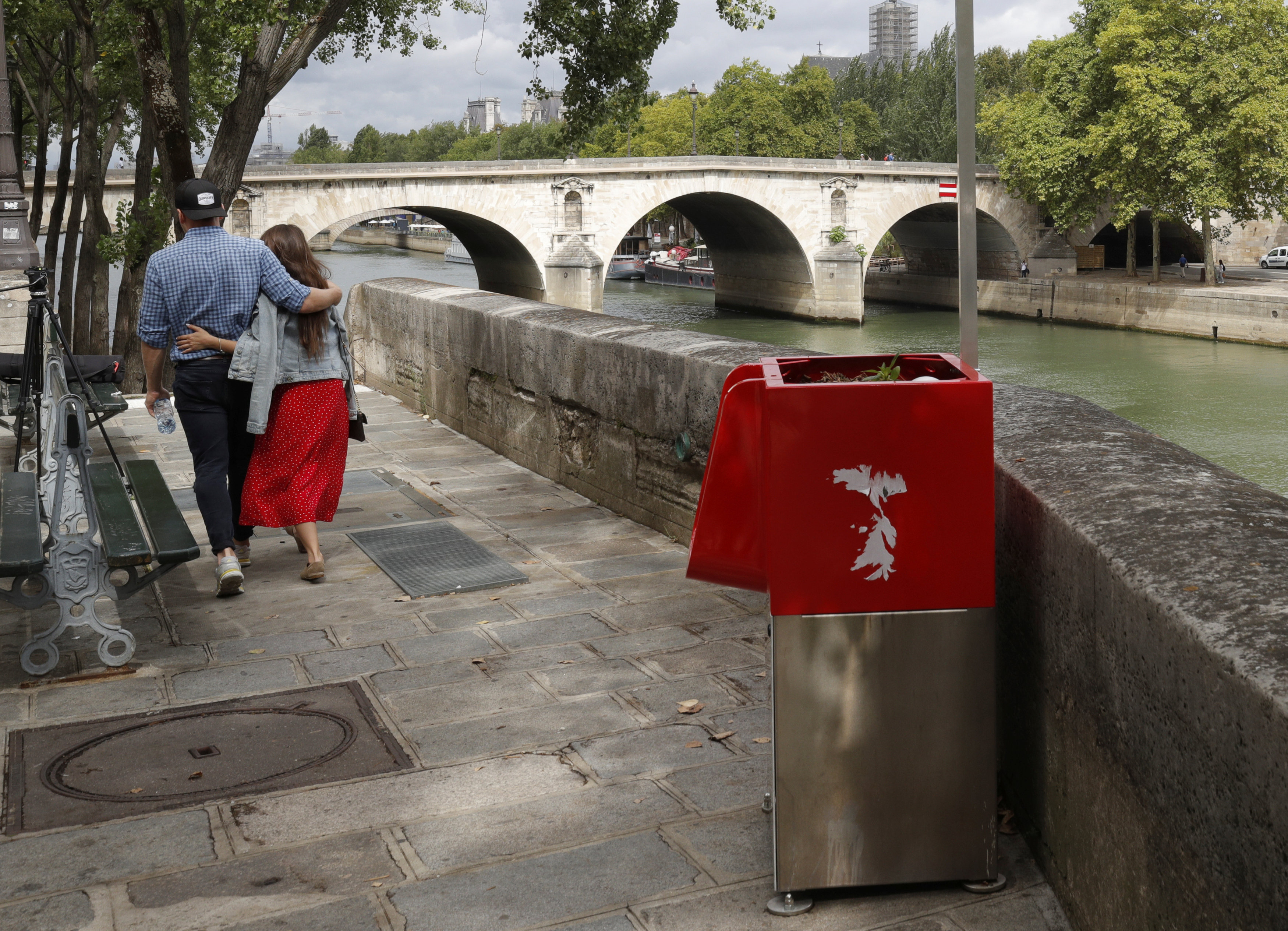 A couple walks near a bright red, eco-friendly urinal on the Ile Saint-Louis along the Seine River in Paris