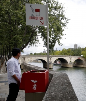 A journalist poses in front of a bright red, eco-friendly urinal on the Ile Saint-Louis along the Seine River in Paris