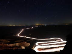 Cars drive through Ramon Crater during the Perseid meteor shower near the town of Mitzpe Ramonin