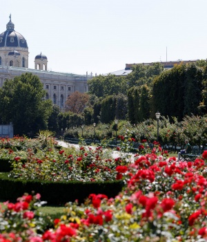 A woman rests in a public garden next to the Natural History Museum in Vienna