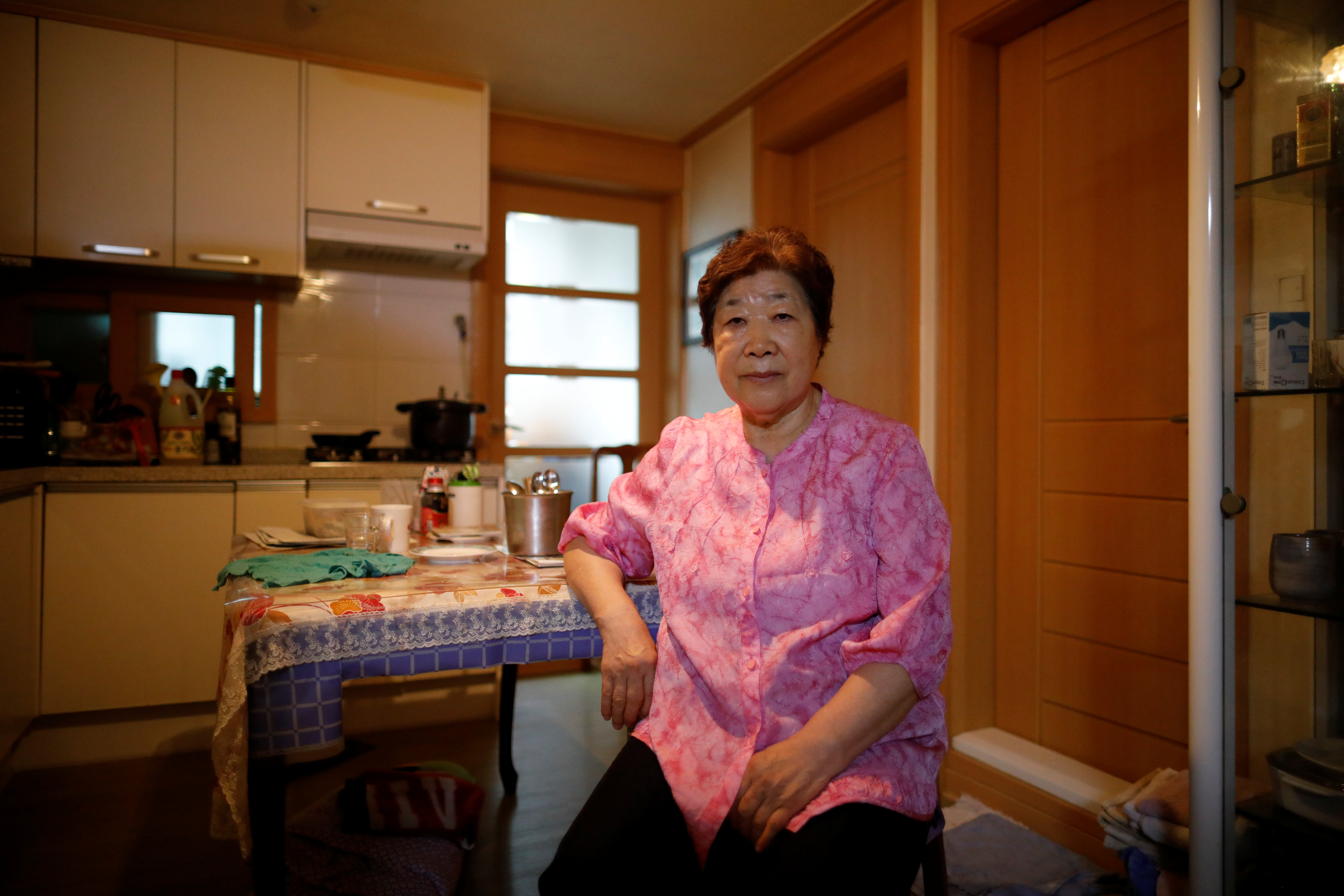 Bae Soon-hui poses for photographs after an interview with Reuters at her home in Seoul