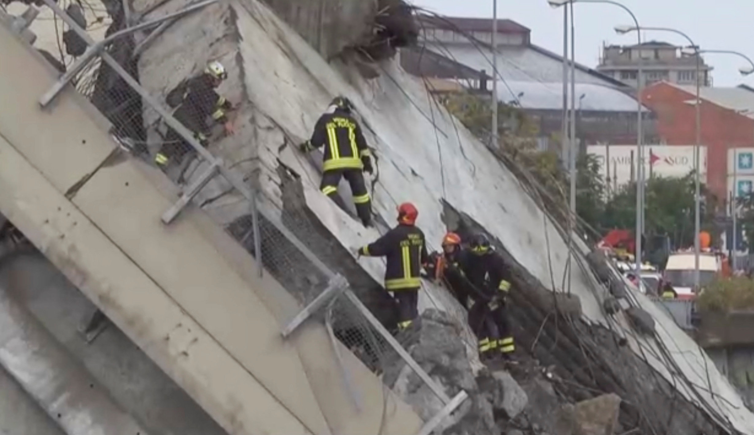Rescue workers are seen at the collapsed Morandi Bridge in the Italian port city of Genoa