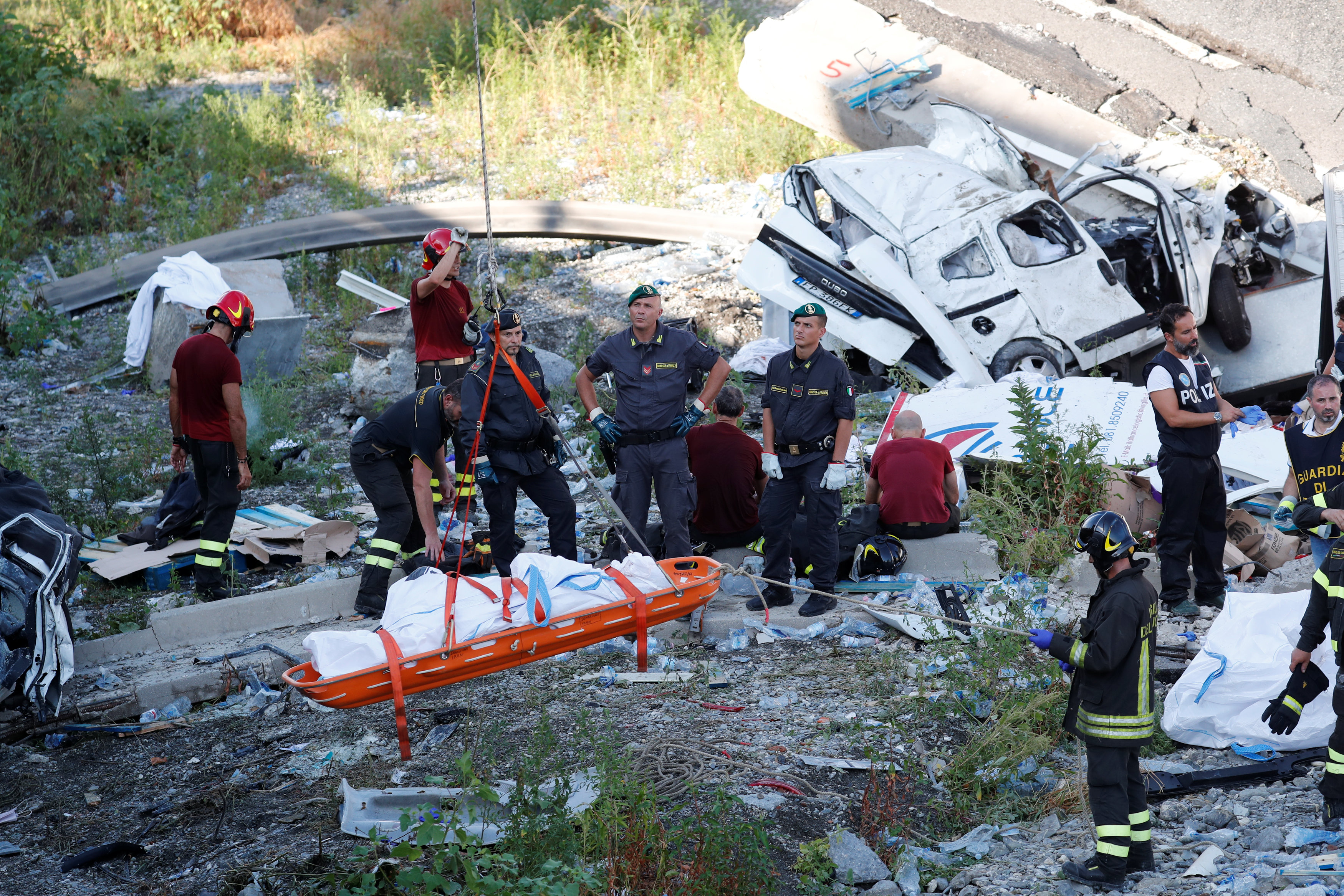 Rescue workers recover a body at the site of the collapsed Morandi Bridge in the Italian port city of Genoa