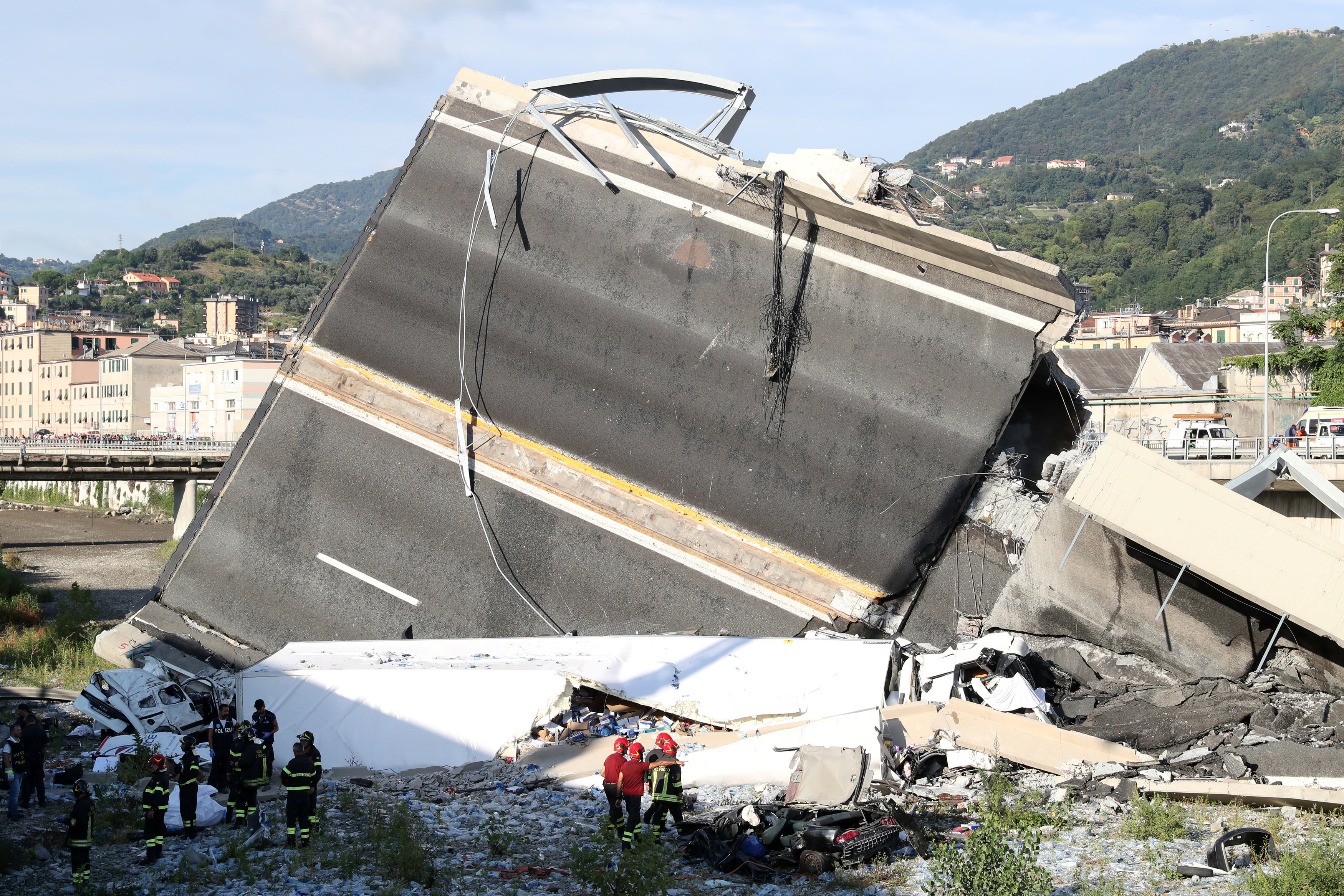 Firefighters and rescue workers stand next to collapsed motorway Morandi Bridge site in Genoa